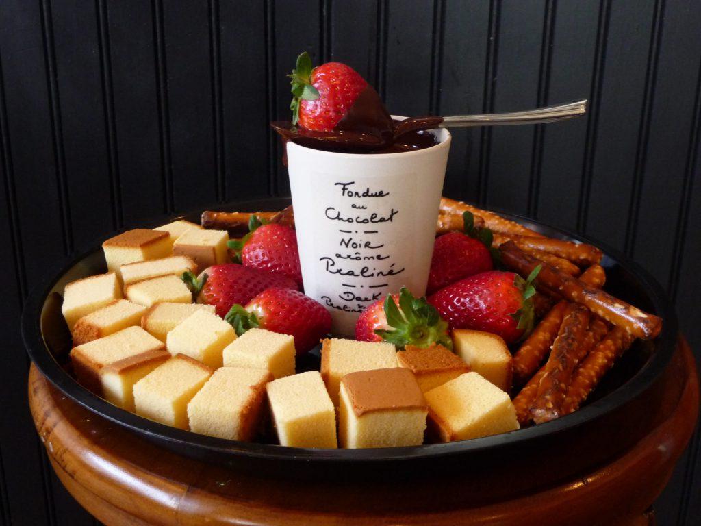 Schokoladenfondue in einer Tasse mit frischen Erdbeeren und Kuchen